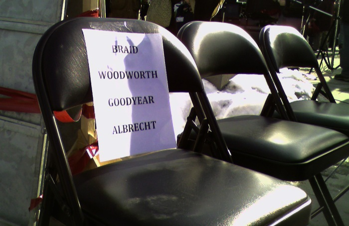 A sign taped to the vacant seats lists the names of the absent Conservative MPs: Braid, Woodworth, Goodyear, Albrecht