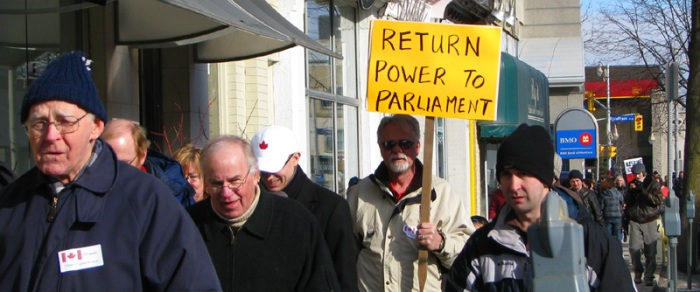 Sign in the crowd of Marchers reads: return power to parliament