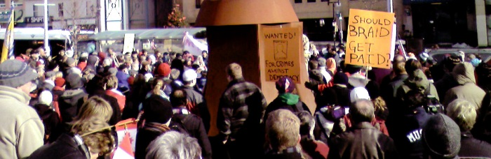 One sign poses the question: Should Braid Get Paid? And another says; WANTED - Stephen Harper - For Crimes Against Democracy