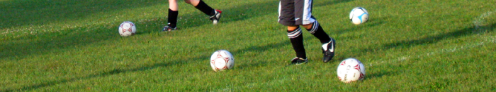 soccer balls interspersed with the feet of a few soccer players on a practice field