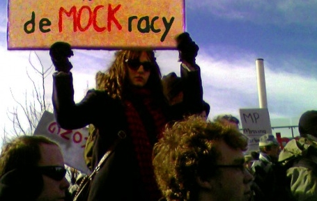 "woman holds a sign reading ""demockracy"" overhead at a cold weather rally"