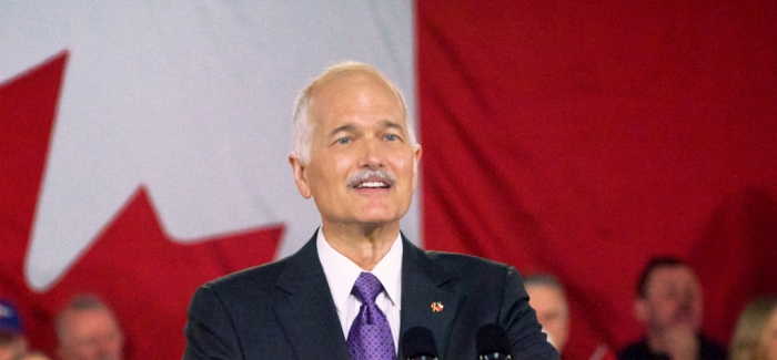 Jack Layton at rally, standing in front of flag.