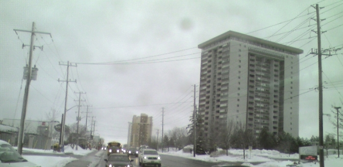 urban street with 70's era apartment tower and hydro poles