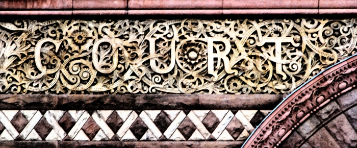 "The word ""Court"" intertwined in the fascia above the side entrance to Toronto's Old City Hall from the day"