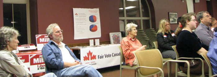 looking at the back couple of rows of audience; the Fair Vote table on display behind
