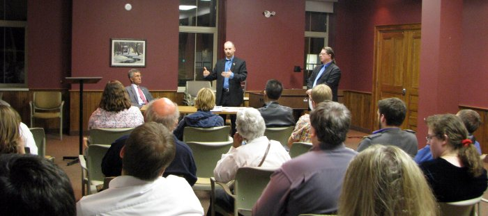 Over the heads of the audience; Satnik stands front and center, flanked by Ron Oberth seated at left and moderator Bob Jonkman standing at right.