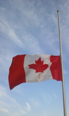A Canadian flag flies at half mast against a blue sky