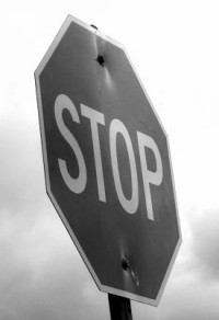 black and white image of a stop sign at an angle