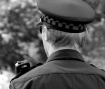 black and white head and shoulders photo of uniformed officer from behind