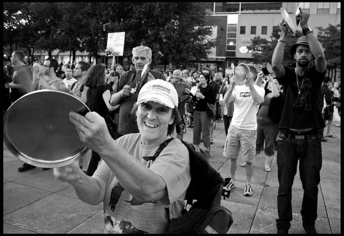 black and white photograph of citizens of all ages banging on casseroles