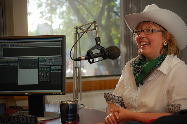 Ms.  May wearing a cowboy hat, on the radio