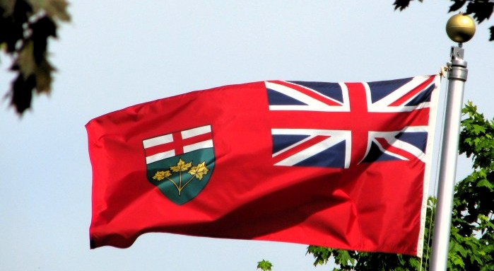 the Ontario flag flag flies against a blue sky