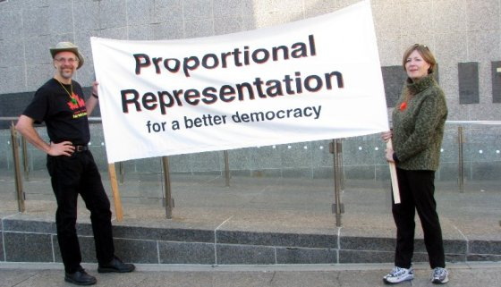 "Organizers Byron Weber Becker and Sharon Sommerville hold a ""Proportional representation for a better democracy banner."
